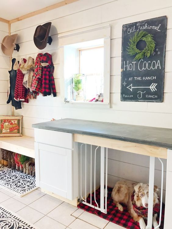a farmhouse entryway with a built-in bench and a built-in dog kennel with a plaid cushion and a black countertop to use it as a table