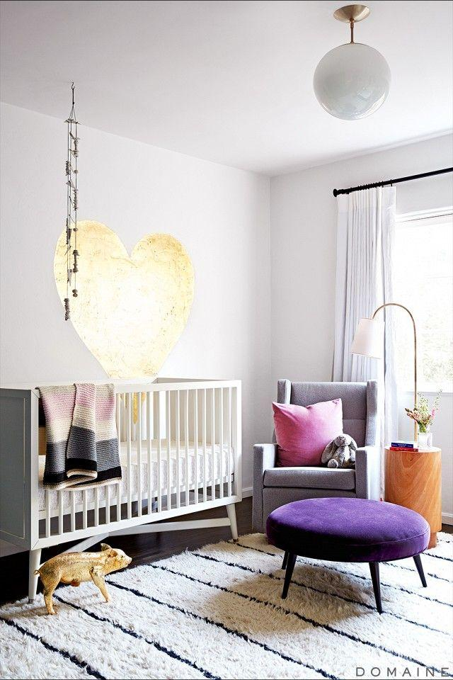 a gorgeous modern nursery with a white crib, a gold heart on the wall, a grey chair with a pink pillow and a purple ottoman is cool