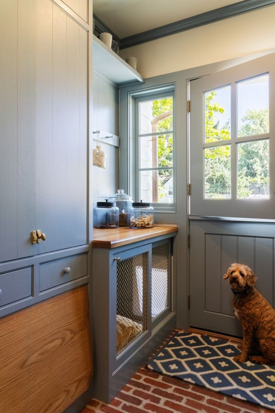 a grey entryway with elegant cabinetry and shelves plus a dog kennel with a mattress and a sliding door and an exit outside