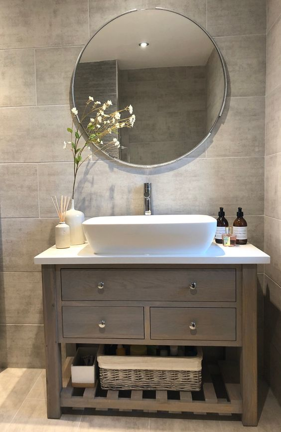 a grey tile bathroom with a taupe vanity, a white sink, a round mirror, baskets for storage is a very chic and cool idea to rock