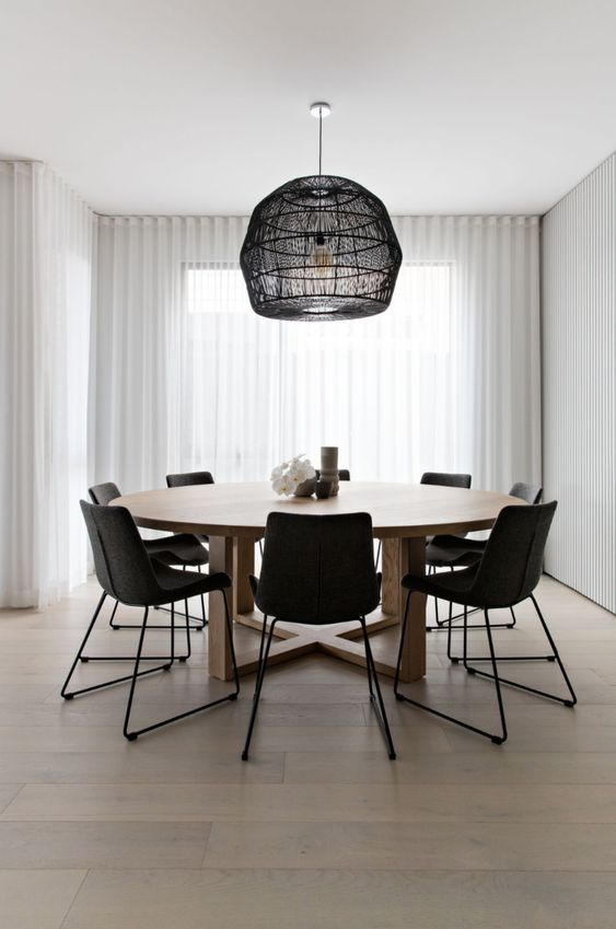 a laconic contemporary dining room with a round table, black chairs, a pendant lamp with a black woven lampshade is amazing