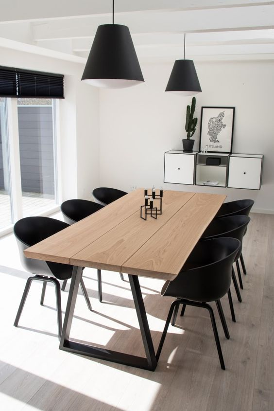 a laconic contemporary dining space with a wooden dining table, black chairs, black pendant lamps and a floating storage unit
