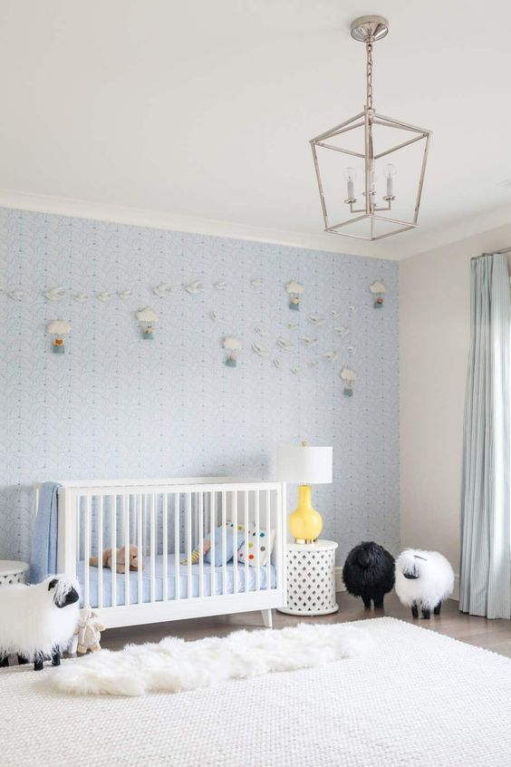 a light blue contemporary nursery with a blue accent wall with air balloons, a white crib and side tales, layered rugs and sheep toys