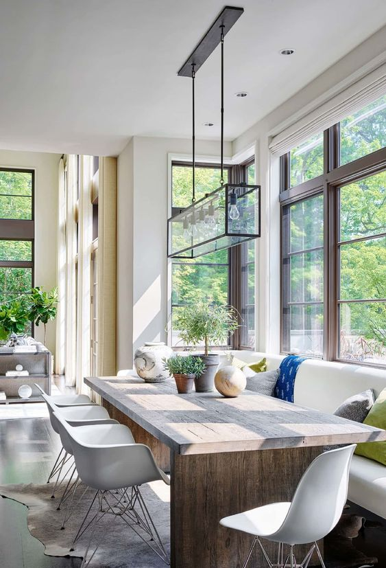 a light-filled contemporary dining room with forest views, a built-in bench, a wooden table, white chairs, a glass chandelier and potted plants