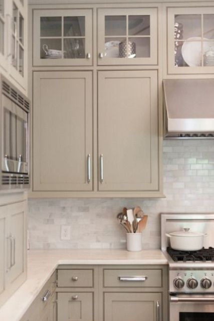 a lovely and cozy taupe kitchen with white marble tiles, with glass and usual cabinets, white stone countertops is a chic and welcoming space