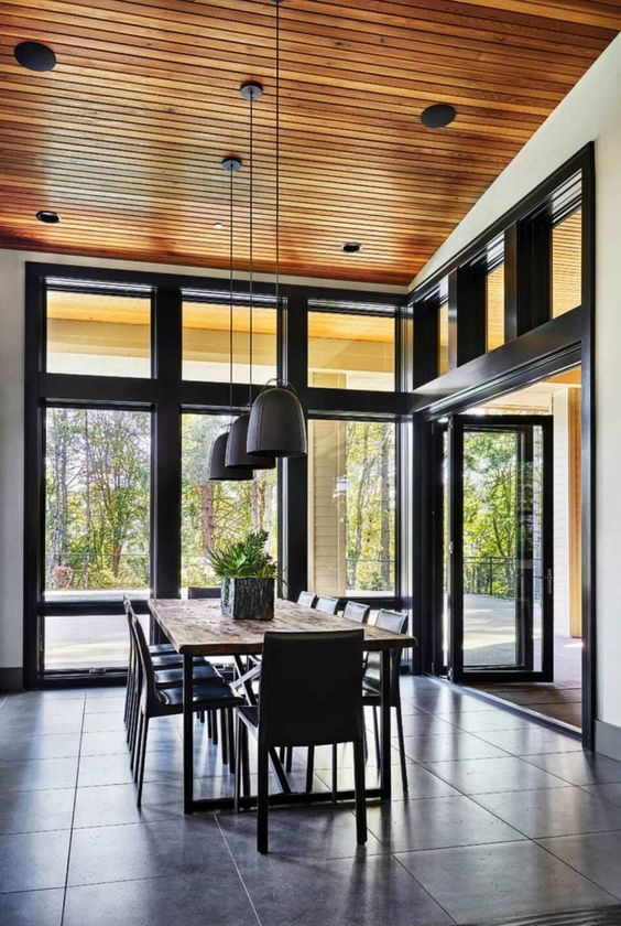 a lovely and simple contemporary dining room with a view of the forest, a simple stained table and black chairs, black pendant lamps