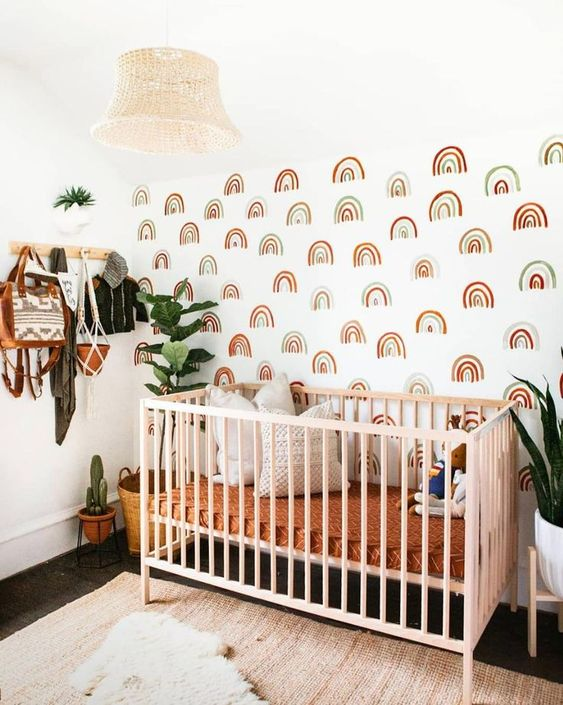 a lovely boho nursery with a rainbow accent wall, a pink crib, bright bedding, layered rugs, a bead pendant lamp and statement plants