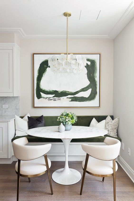 a lovely contemporary dining nook with a green built-in bench, an oval table, creamy chairs, a refined chandelier and a green artwork