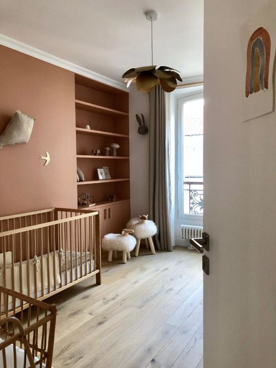 a lovely contemporary nursery in muted color, with a rust accent wall and built-in shelves, stained cribs, faux fur stools and grey curtains