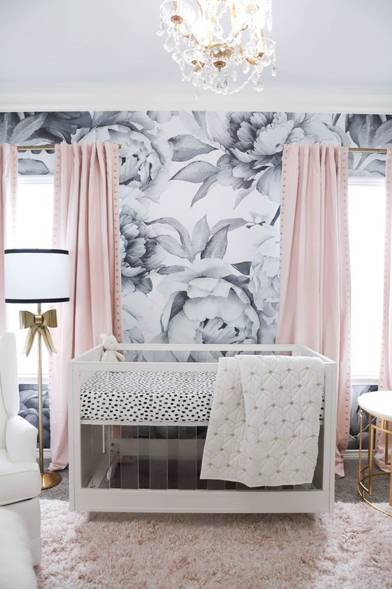 a lovely contemporary nursery with a floral print accent wall, pink curtains, an acrylic crib, gold touches and a white chair is cool