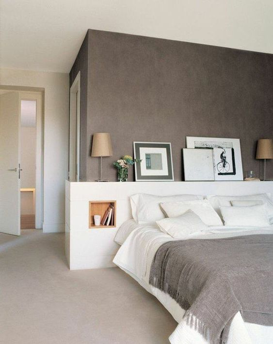 a lovely modern bedroom with a taupe accent wall, a white bed with a storage headboard, artworks and lamps and white bedding