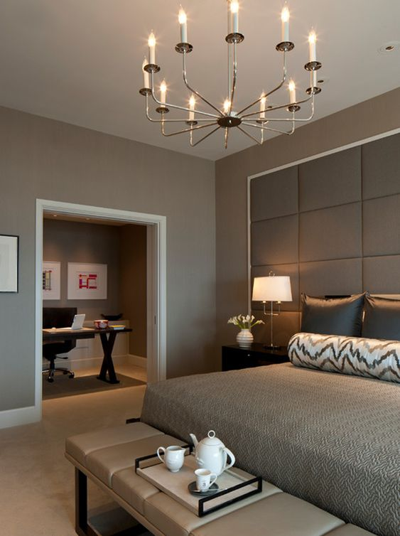 a lovely modern bedroom with taupe walls, a bed with an oversized upholstered headboard, an upholstered bench and a lovely chandelier
