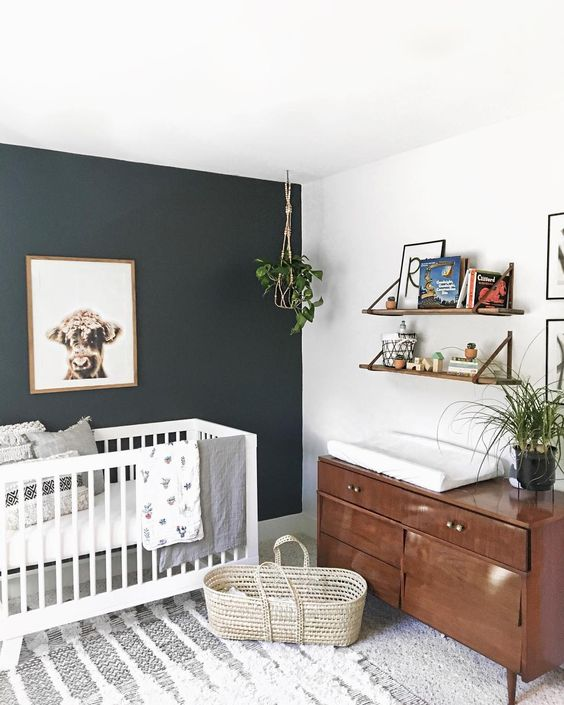 a lovely modern nursery with a black accent wall, a white crib, a rich-stained dresser, open shelves, potted plants, a boho rug and printed bedding