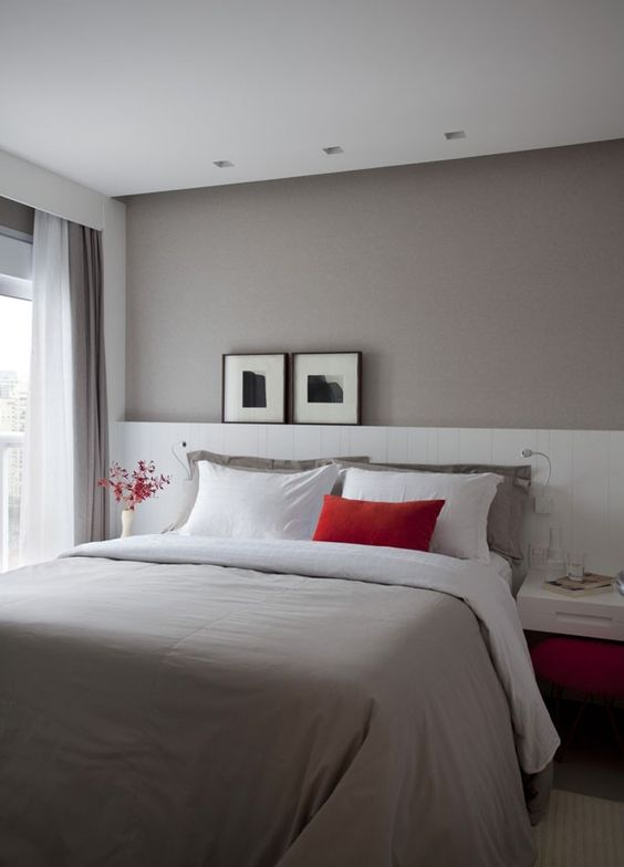a lovely small bedroom with a taupe accent wall, a bed with an extended white headboard, floating nightstands and touches of red