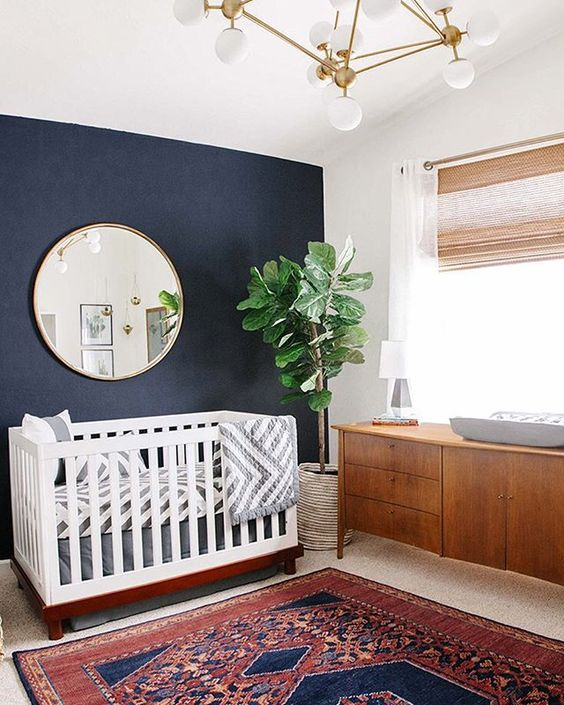a mid-century modern nursery with a navy accent wall, a crib with printed bedding, a rich-stained changing table, a colorful printed rug and a chic chandelier