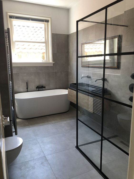 a minimalist bathroom clad with large scale taupe tiles, with an oval tub, a black double sink and black fixtures is very chic