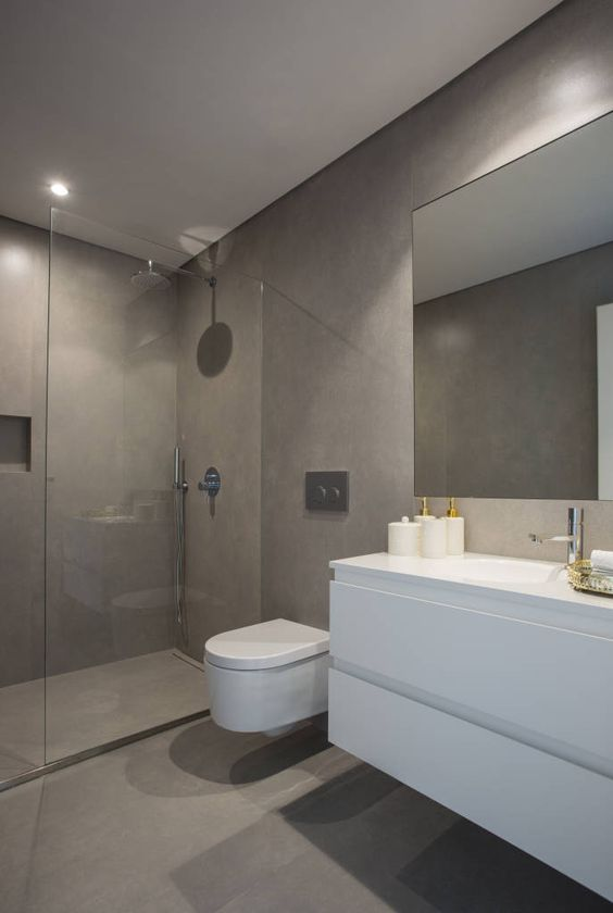 a minimalist taupe bathroom with concrete walls, floor and a shower space, a white floating vanity, a large mirror and white appliances