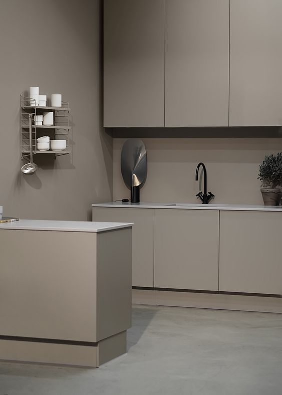 a minimalist taupe kitchen with sleek matte cabinets, a taupe backsplash and white countertops, an open shelf and black fixtures is gorgeous