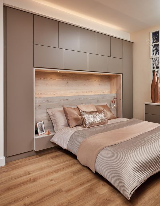 a modern bedroom with a taupe sleek storage unit, a retrasting bed, taupe and blush bedding, a taupe dresser is very welcoming