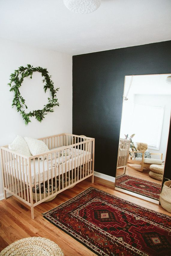 a modern boho nursery with a black accent wall, a stained crib and chair, a floor mirror, a printed rug, neutral bedding and a greenery wreath