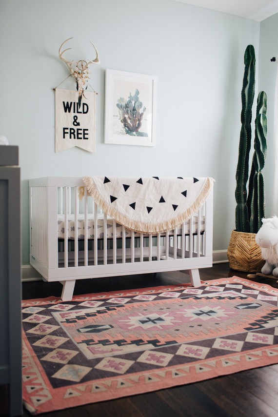 a modern boho nursery with a printed rug and blanket, a cool desert gallery wall, a statement cactus in a wooden planter and a grey dresser