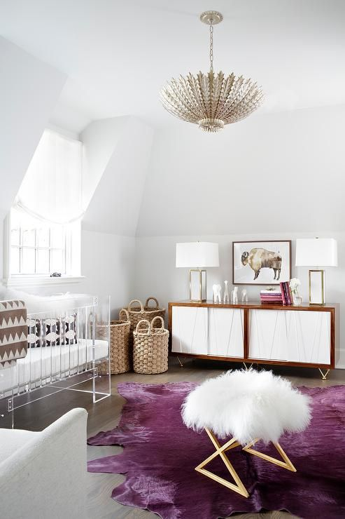 a modern glam nursery with an acrylic crib, a fluffy pouf, a white and stained credenza, baskets for storage and a purple statement rug