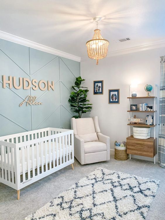 a modern nursery with a green paneled accent wall, a white crib and chair, a shelf unit with a cabinet, a potted plant and a pendant lamp