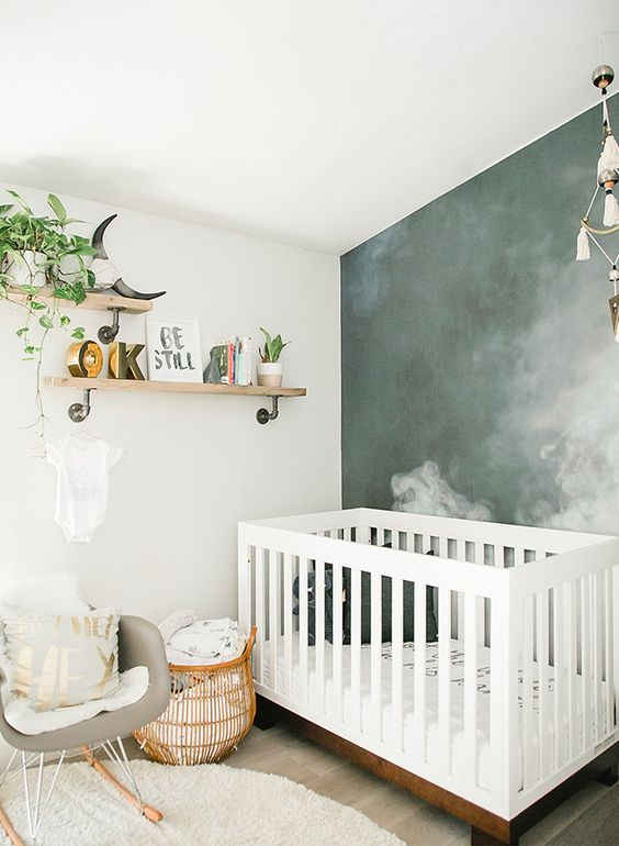 a modern small nursery with a grey chair, a white crib, open shelves, a smoke accent wall, a rattan basket for storage is amazing