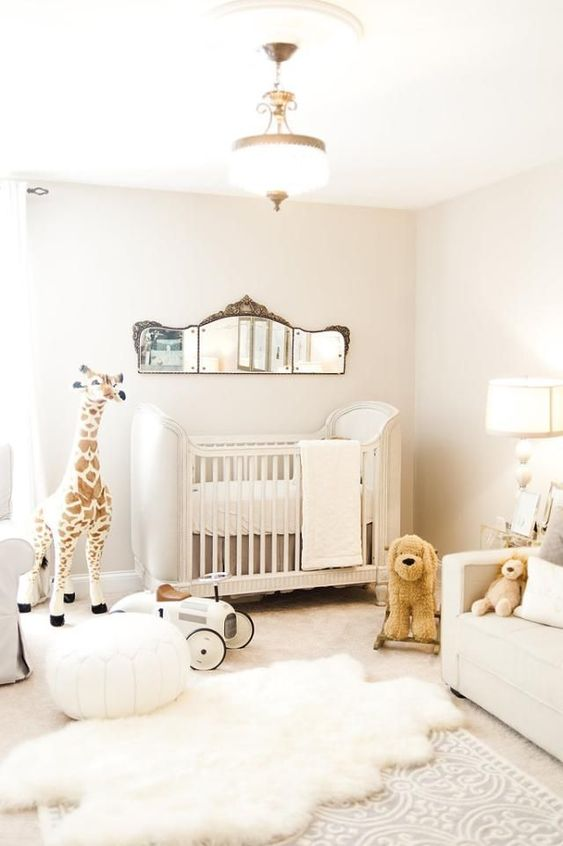 a neutral contemporary nursery with a catchy crib, a creamy sofa, layered rugs, toys, a vintage mirror and some lamps