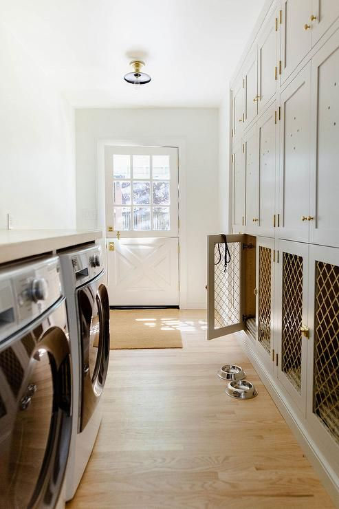 a neutral laundry room with shaker cabinets and lower cabinets turned into a multiple dog crate is a lovely solution