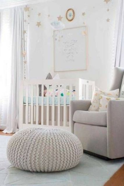 a neutral nursery with a star accent wall, a white crib with star pillows, a grey chair and a chunky knit pouf and star buntings is cool