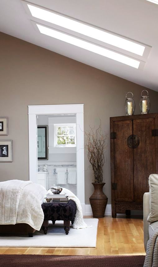 a cozy attic bedroom with taupe walls
