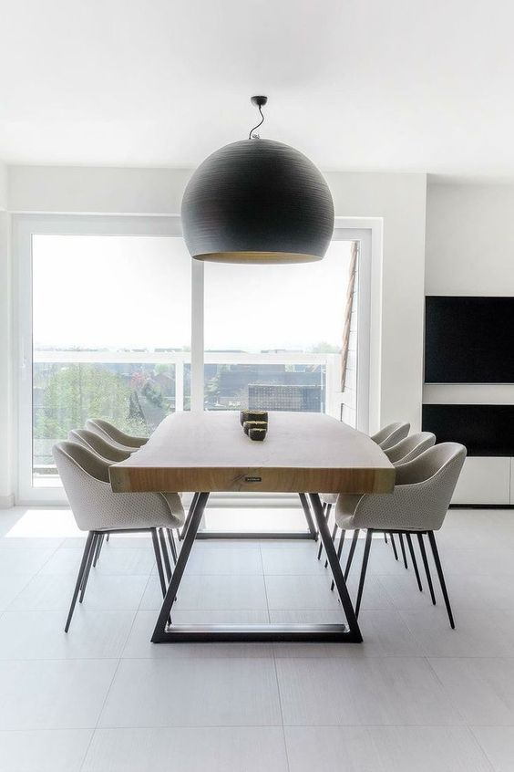 a pretty contemporary dining space with a living edge table, neutral chairs and a statement black pendant lamp is very cool