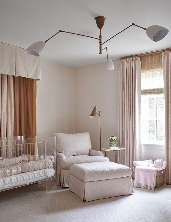 a pretty contemporary nursery in nrutrals, with an acrylic crib, a neutral chair and a footrest, a basket and neutral curtains