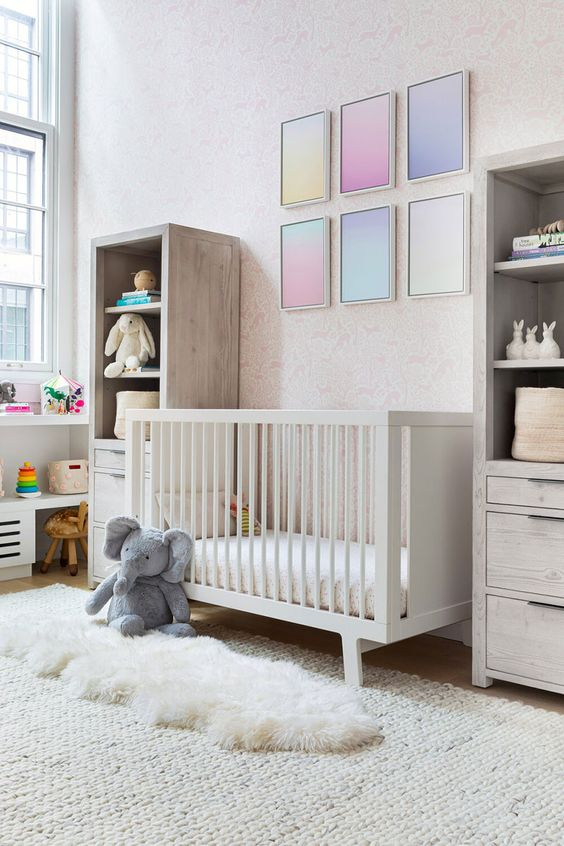 a pretty contemporary nursery with a pink printed wall, neutral furniture, layered rugs, lovely toys and a desk for the kid