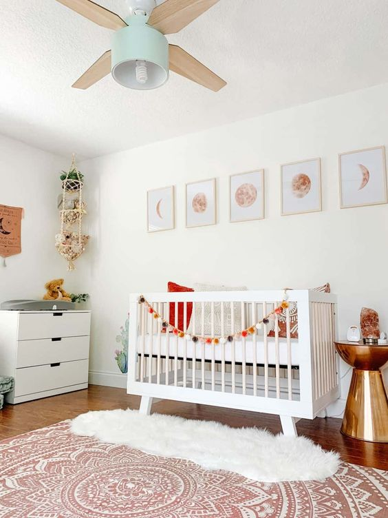 a pretty modern nursery with white furniture, moon prints, a lamp and a fan, a hanging shelf with toys, layered rugs and a shiny side table