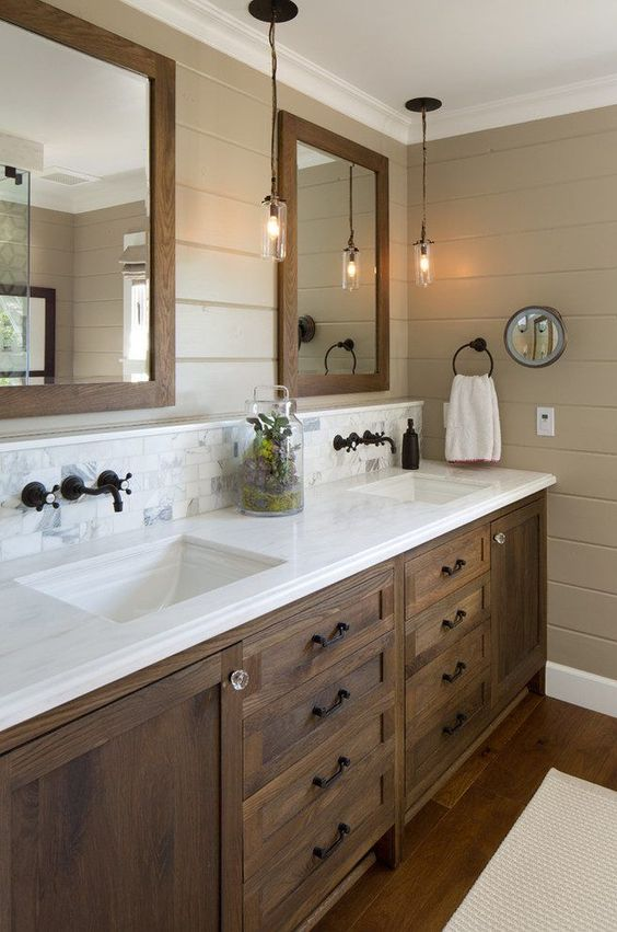 a pretty rustic bathroom with taupe planked walls, a rich-stained wooden vanity, a white countertop, mirrors in wooden frame and pendant lamps