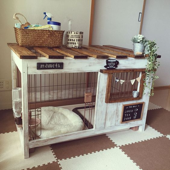 a pretty whitewashed dog kennel with a cushion, a bowl with water, use for storage on top and decorated with bunting
