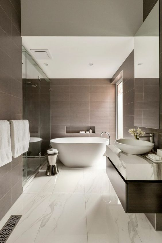 a refined bathroom with taupe and white marble tiles, a large shower space and an oval tub, a dark stained vanity and a large window for natural light
