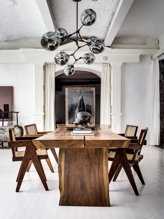 a refined contemporary dining space with a living edge table, rattan and wooden chairs, a beautiful black chandelier and rocks
