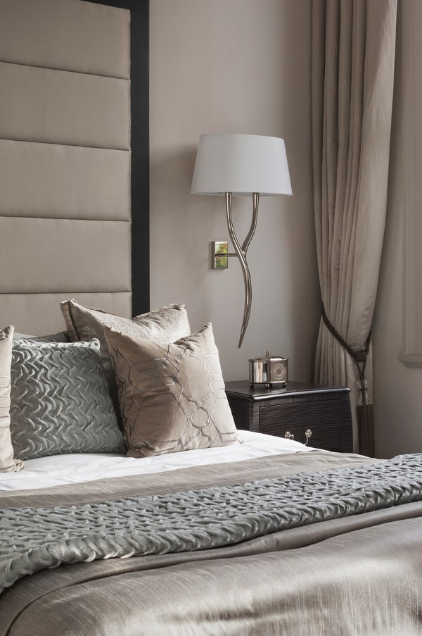 a refined taupe bedroom with a bed with an oversized upholstered headboard, a dark nightstand, a chic sconce and taupe and white bedding