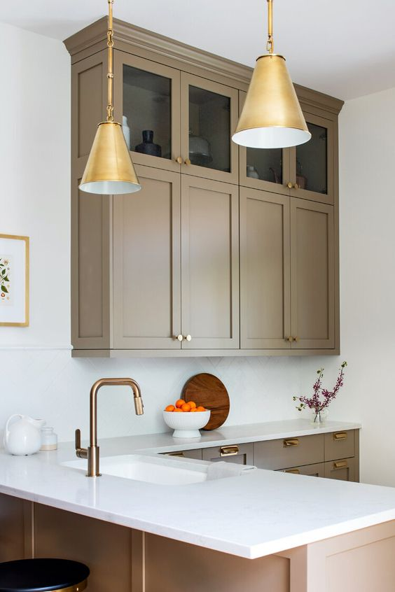 a refined taupe kitchen with shaker cabinets - mostly lower and a couple of upper ones, white stone countertops and a backsplash, gold pendant lamps