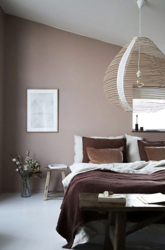 a relaxed bedroom with a taupe accent wall, a wooden bed and stools, an oversized wooden lampshade and some art