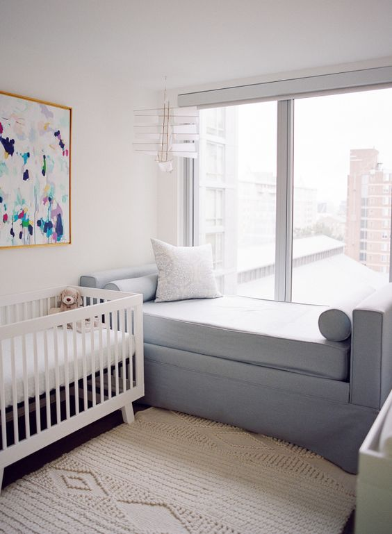a simple contemporary nursery with a white crib, a colorful artwork, a grey daybed, a neutral rug and a view of the city