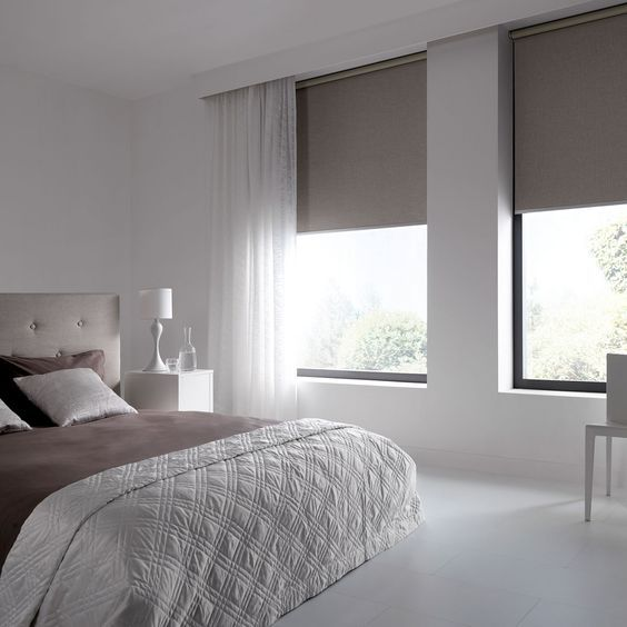 a small white bedroom with a tan upholstered bed, taupe bedding and matching sleek shades and a chair is a very chic idea