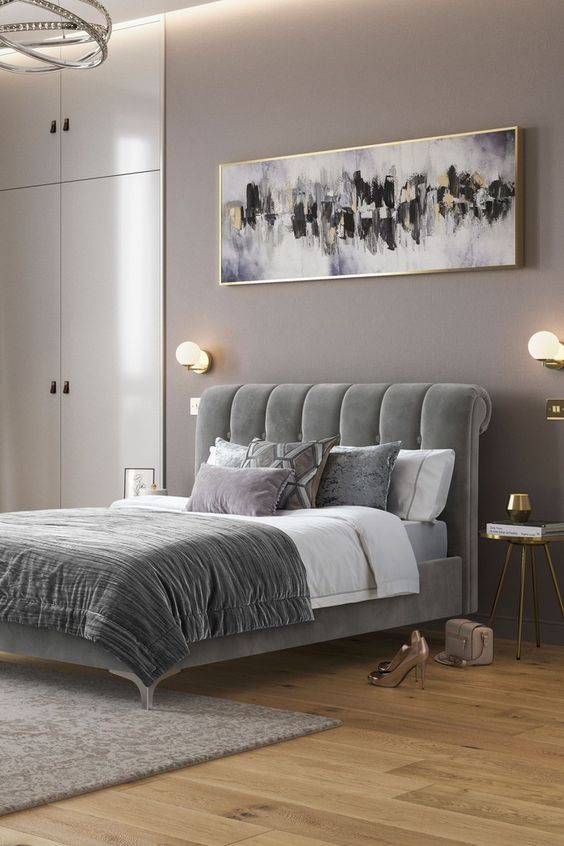 a sophisticated taupe bedroom with built-in wardrobes, a grey upholstered bed with grey bedding, a statement artwork and some lights
