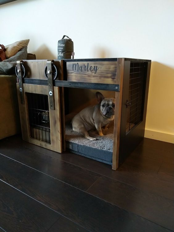 a stained wood and blackened metal dog crate with a sliding door is a cool solution for an industrial or rustic space