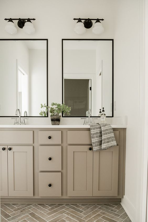 a stylish bathroom with a grey chevron tile floor, a taupe double vanity, two mirrors, sconces and a potted plant is a very chic idea