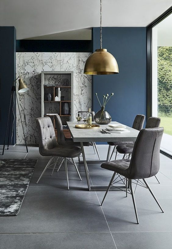 a stylish contemporary dining room with a glazed wall, a concrete table, grey upholstered chairs, a gold pendant lamp and candles