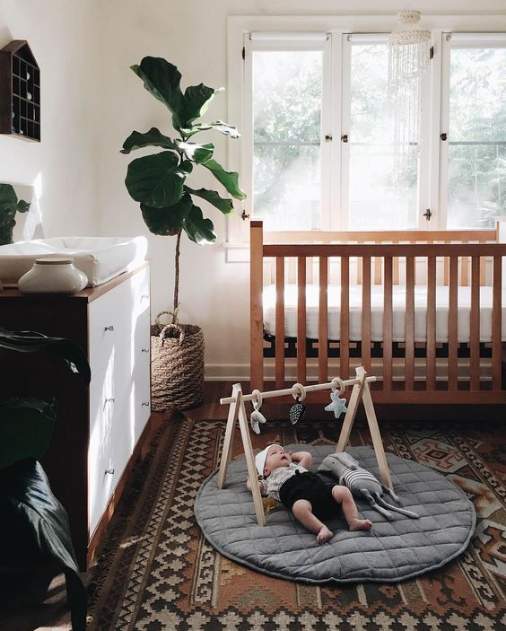 a stylish modern boho nursery with a stained crib, a stained and white dresser, a printed rug, a house-shaped shelf and statement plants